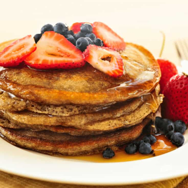 plate of pancakes topped with syrup, blueberries and strawberries