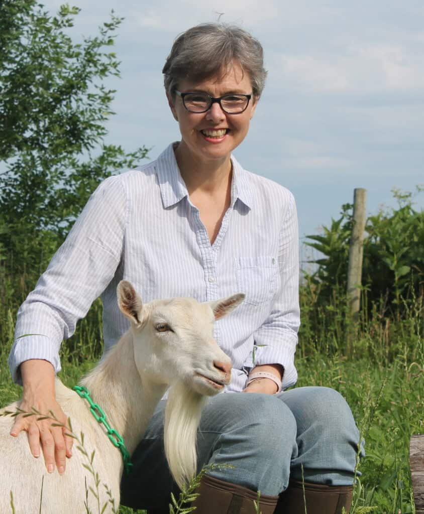 Deborah of Thrifty Homesteader smiling, sitting next to a white goat