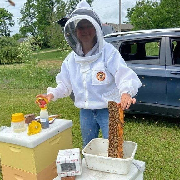 Dr. Tammy Horn Potter tending to beehive
